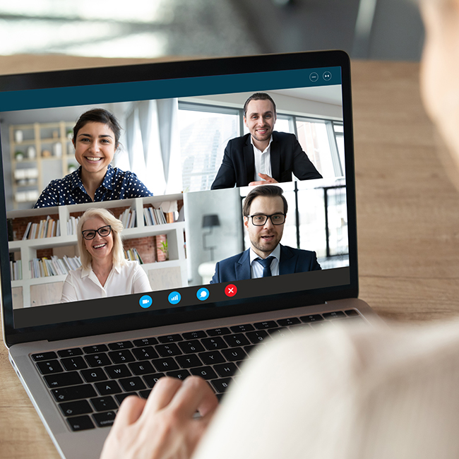 View over female shoulder at computer webcam screen view of four different age and ethnicity business people negotiating distantly using video conference app, video call virtual communication concept